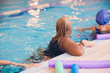 Young Muslim Girl Swimming At Pool Brown Clothes.