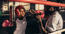 Boy Practicing Box With Coach In Boxing Ring