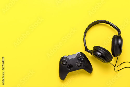 Photo  Black headphones and a gamepad on yellow background