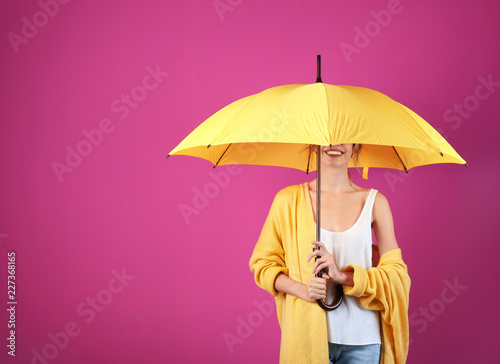 Woman with yellow umbrella on color background. Space for text