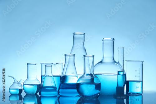 Fotografija Laboratory glassware with liquid on table against color background