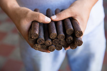 Hand Holding Cigars.
