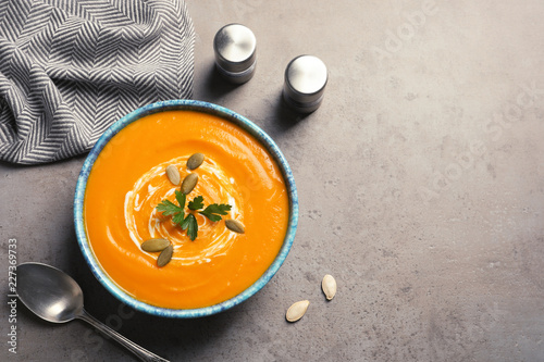 Flat lay composition with bowl of pumpkin soup and space for text on gray background