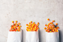 Flat Lay Composition With Paper Bags Of Delicious Candies And Space For Text On Gray Background