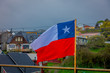 Outdoor view of Chilean flag waving with beautiful and colorful houses on stilts palafitos behind in the horizont in Castro, Chiloe Island