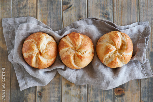 Photographie Three crusty round bread rolls in a row on linen towel on rustic wooden backgrou