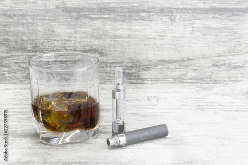 Fotobehang Alcohol Whiskey in a glass with an e-cigarette and liquid for it on a gray stone background