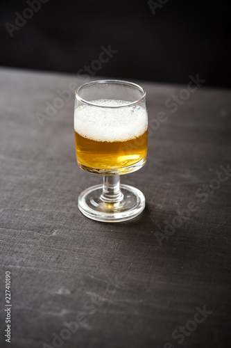 one glass of delicious beer on an old black wooden table in a pub