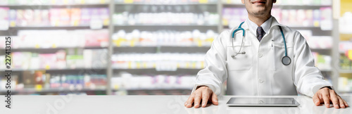Male pharmacist sitting at table with tablet computer in pharmacy office. Medical healthcare staff and drugstore business.