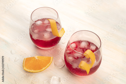 Staande foto Cocktail Two vibrant cocktails with campari and orange zest garnishes, with ice cubes on a light background, with copy space