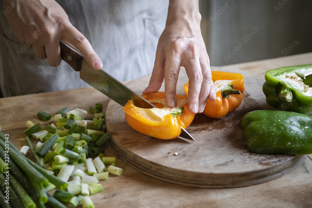 Fototapety, obrazy: Cook slicing bell peppers on a cutting board