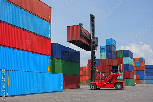 Fotografía  Forklift reach stacker is lifting 40' high cube container in the depot
