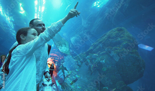 Teenage girl with Dad amusingly watching the fish in Aquarium