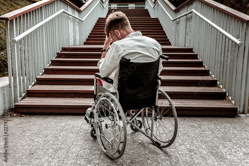 Obraz Many stairs. Horizontal image of depressed disabled man sitting in the wheelchair and facing the difficulties with climbing the stairs alone - fototapety do salonu
