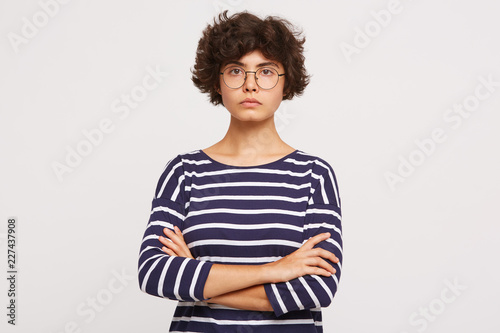 Fotografija  Closeup of calm serious emotionless young curly brownhair woman wears white and