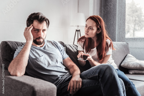 Family quarrel. Unhappy nice young woman holding a smartphone and talking to her husband while being jealous