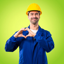 Young Workman With Helmet Making Heart Symbol By Hands. Being In Love On Green Background