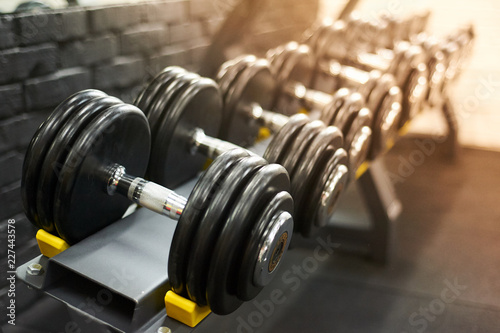 Fotografia dumbbells row in a gym. sport sunny background