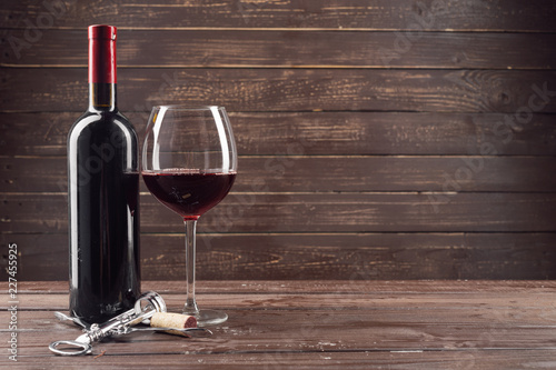 Wine bottle and grape on wooden table