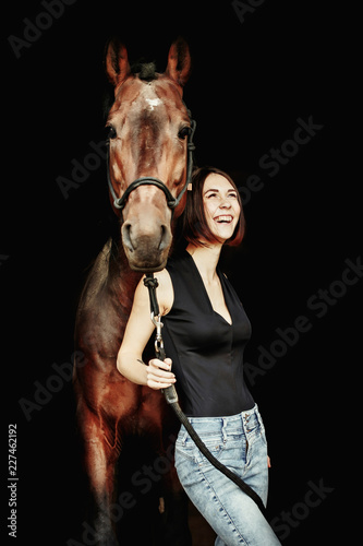 Fototapeta Portrait of smiling pretty woman standing by horse on the black background. Isolate obraz