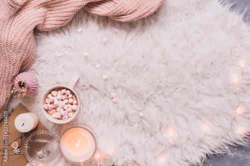 Cozy background. Mug of hot cocoa or hot chocolate with marshmallow on white rug. Copy space
