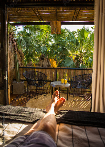 Fotografie, Obraz  Resort balcony in trees with feet and beer