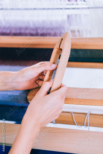 Fotografie, Obraz  Female hands holding a needle for weaving against the background of a loom, lila