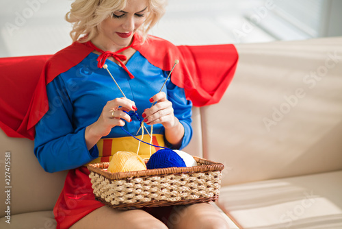 Young beautiful blond Caucasian woman wearing superwoman costume knitting while Wallpaper Mural