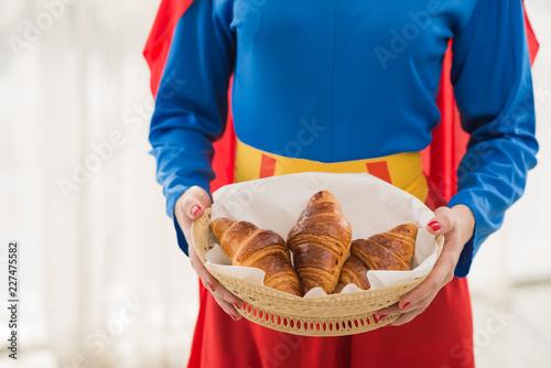 Unrecognizable female wearing superwoman costume holding basket of appetizing fr Canvas Print