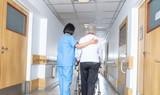 Asian doctor helping elder woman with walker in hospital hallway - 227476541