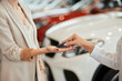 Close up of seller and customer female hands passing the key of a new car at dealership over blurred car background.