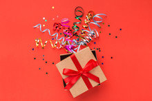 Gift Box With Colourful Streamers On Red Background