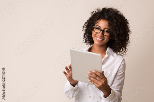 Fotografia  Happy businesswoman using tablet over light background