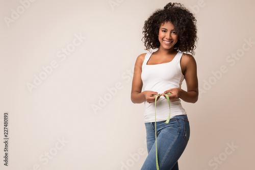 Obraz Happy african-american woman measuring waist with tape - fototapety do salonu