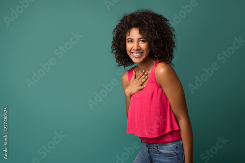 Fotografía  Cheerful african-american woman holding hand on chest