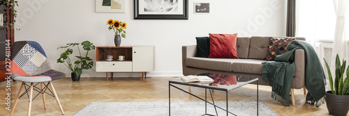 Horizontal photo of a living room interior with a sofa, table, sunflowers and patterned chair. Real photo