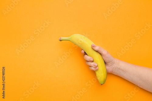 Female hand holding banana on orange background