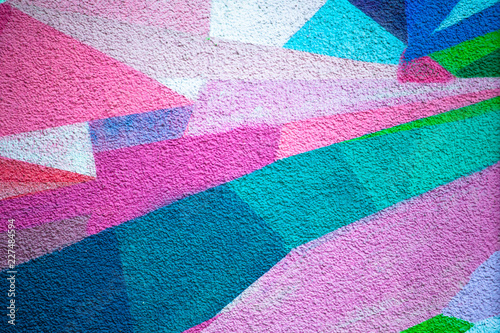 Poster Graffiti plastered bright wall, decorated with geometric patterns in different colors, background, texture