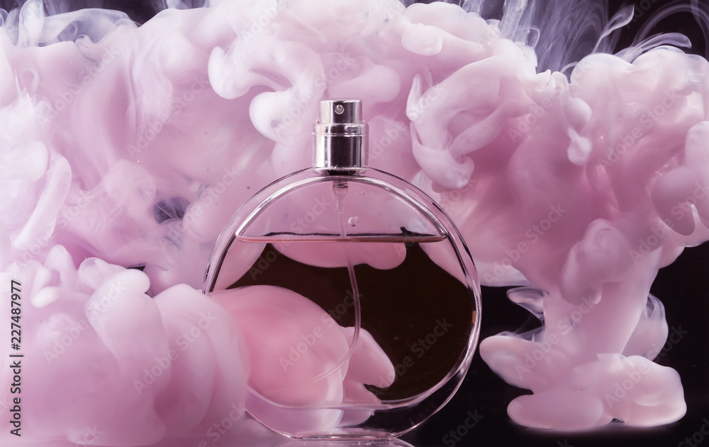 Fototapety, obrazy: Bottle of perfume in color smoke on dark background