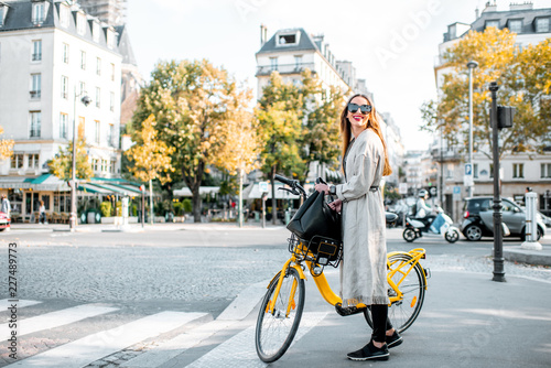 Obraz Portrait of a young stylish woman with yellow bicycle on the street in Paris - fototapety do salonu