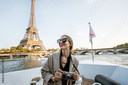 Poster Paris Young woman enjoying beautiful landscape view on the riverside with Eiffel tower from the boat during the sunset in Paris