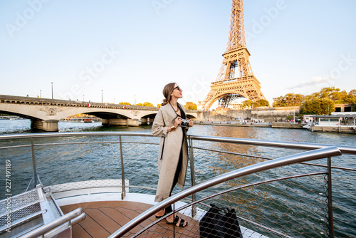 Obraz Young woman enjoying beautiful landscape view on the riverside with Eiffel tower from the boat during the sunset in Paris - fototapety do salonu