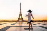 Fototapeta Fototapety Paryż - Woman dressed in coat and hat walking on the famous square with great view on the Eiffel tower early in the morning in Paris