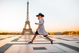 Fototapeta Fototapety z wieżą Eiffla - Woman jumping on the famous square with great view on the Eiffel tower early in the morning in Paris