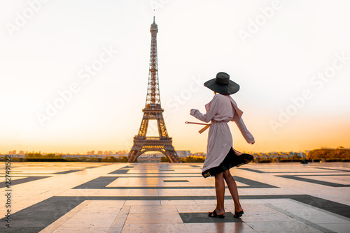 Woman dressed in coat and hat walking on the famous square with great view on the Eiffel tower early in the morning in Paris - 227491522