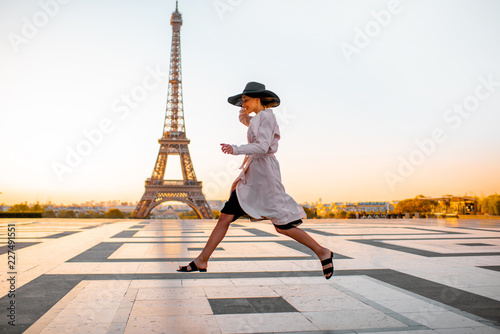 Woman jumping on the famous square with great view on the Eiffel tower early in the morning in Paris
