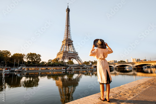 Young woman tourist enjoying landscape view on the Eiffel tower with beautiful reflection on the water during the mornign light in Paris