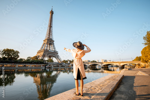 Fototapeta Young woman tourist enjoying landscape view on the Eiffel tower with beautiful reflection on the water during the mornign light in Paris obraz