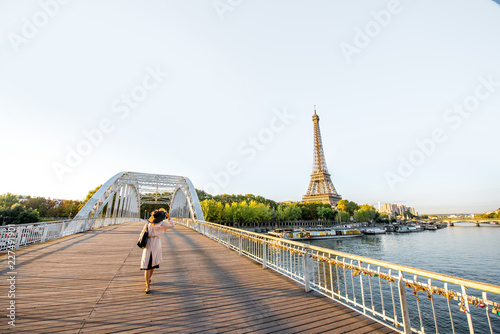 Fotografiet Landscape view on the river and Eiffel tower with woman walking on the footbridg