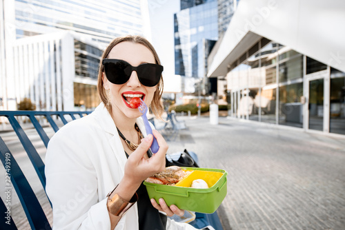 Business woman having a snack with lunch box during a break sitting outdoors at Canvas Print